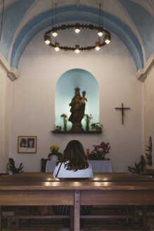 Young woman sitting on bench in church - AFV00549