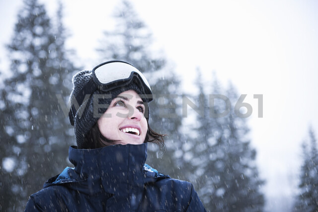 Portrait of young woman wearing ski goggles looking up at snow, Brighton Ski Resort outside of Salt Lake City, Utah, USA - CUF19105