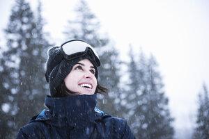 Portrait of young woman wearing ski goggles looking up at snow, Brighton Ski Resort outside of Salt Lake City, Utah, USA - CUF19105
