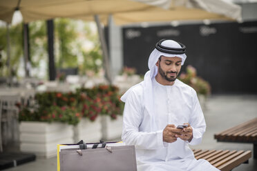 Male shopper  wearing traditional middle eastern clothing sitting on bench reading smartphone text, Dubai, United Arab Emirates - CUF19123