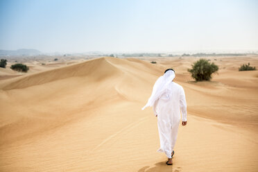 Rear view of middle eastern man wearing traditional clothes walking in desert, Dubai, United Arab Emirates - CUF19132