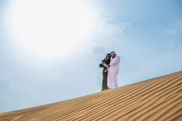 Middle eastern couple wearing traditional clothes taking smartphone selfie on desert dune, Dubai, United Arab Emirates - CUF19138
