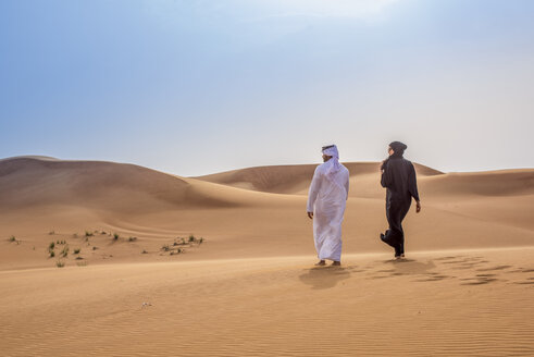Couple wearing traditional middle eastern clothes walking in desert, Dubai, United Arab Emirates - CUF19144