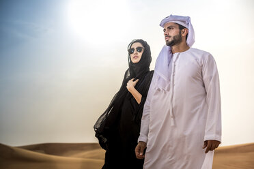 Couple wearing traditional middle eastern clothes in desert, Dubai, United Arab Emirates - CUF19147