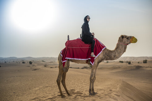 Young woman wearing traditional middle eastern clothes riding camel in desert, Dubai, United Arab Emirates - CUF19153