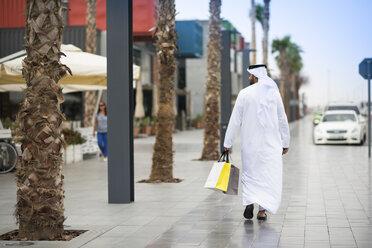 Rear view of man wearing dishdasha walking along street carrying shopping bags, Dubai, United Arab Emirates - CUF19210