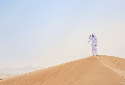Middle eastern man wearing traditional clothes looking out from desert dune, Dubai, United Arab Emirates - CUF19213