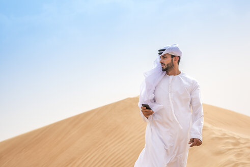 Middle eastern man wearing traditional clothes using smartphone on desert dune, Dubai, United Arab Emirates - CUF19216