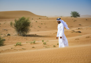 Middle eastern man wearing traditional clothes walking in desert, Dubai, United Arab Emirates - CUF19219