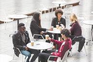 Friends sitting at tables at sidewalk cafe enjoying a coffee - CUF19360