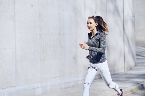 Female runner, concrete wall - BSZF00435