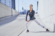 Female runner stretching legs during urban workout - BSZF00441