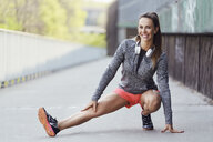 Female runner stretching legs during urban workout - BSZF00447