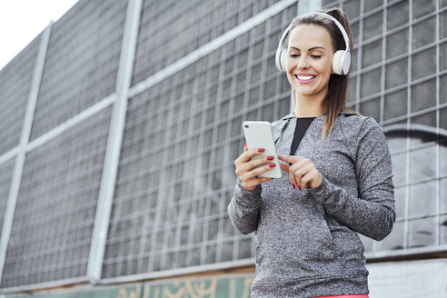 Woman with headphones using smartphone - BSZF00450