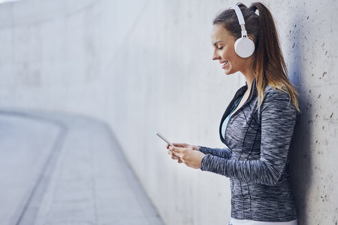 Woman with headphones using smartphone - BSZF00453
