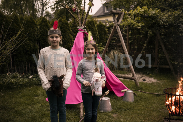 Two girls wearing feather headdress, with stock horse at camp fire - MOEF01215 - Robijn Page/Westend61