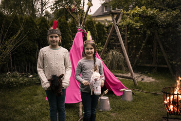 Two girls wearing feather headdress, with stock horse at camp fire - MOEF01215