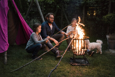 Man and two girls grilling sausage over camp fire in garden - MOEF01218