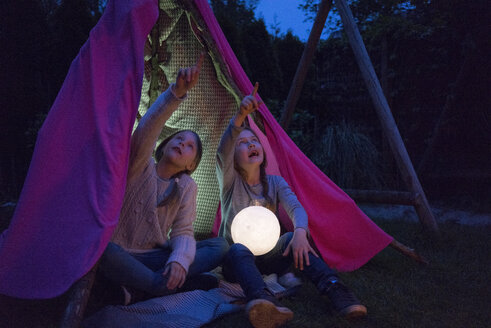 Two girls sitting in tipi, holding lamp as moon - MOEF01221