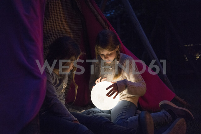 Two girls sitting in tipi, holding lamp as moon - MOEF01224 - Robijn Page/Westend61