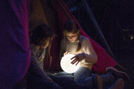 Two girls sitting in tipi, holding lamp as moon - MOEF01224