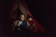 Father and daughters sitting in tent, taking a selfie - MOEF01227