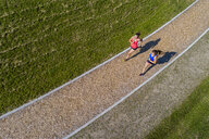 Aerial view of female joggers on woodchip trail - STSF01589