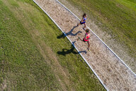 Aerial view of female joggers on woodchip trail - STSF01592