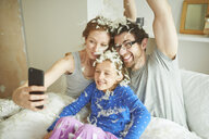 Mid adult couple and daughter covered in pillow fight feathers taking smartphone selfie in bed - CUF19570