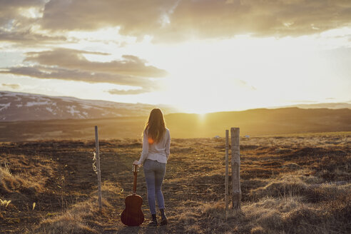 Iceland,  young woman with guitar at sunset - AFVF00554