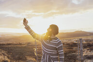 Iceland, young man using smartphone, selfie at sunset - AFVF00557