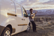 Iceland, young man leaning on van and playing guitar - AFVF00560