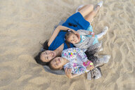 Happy mother with two daughters lying on the beach - AFVF00566