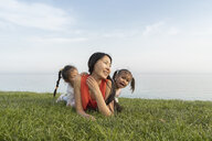 Mother with two daughters lying in grass at the coast - AFVF00575
