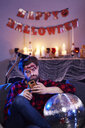 Bored man using mobile phone at Halloween party - ABIF00470