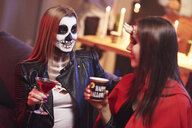 Women in creepy costume drinking at party - ABIF00476