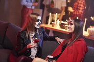 Women in creepy costume drinking at party - ABIF00479