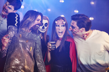 Friends in Halloween costumes dancing among confetti - ABIF00497