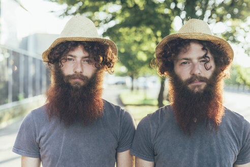 Portrait of identical male hipster twins wearing straw hats on sidewalk - CUF19801