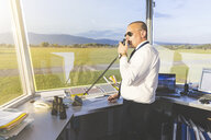 Pilot in control tower of small airport, using telecommunications system - CUF19825