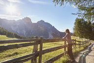 Mature woman leaning against fence looking out at Dolomites, Sexten, South Tyrol, Italy - CUF19948