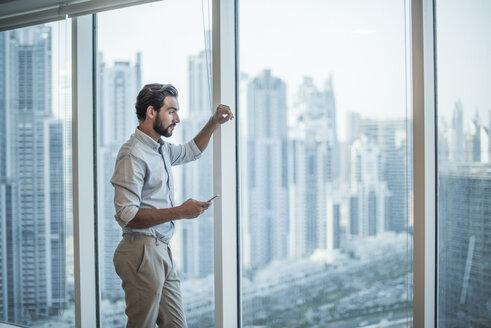 Businessman with smartphone staring through window with skyscraper  view, Dubai, United Arab Emirates - CUF19990