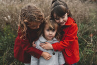 Portrait of two girls hugging toddler sister in field - ISF07434