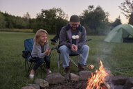 Father and daughter sitting beside campfire, toasting marshmallows over fire - ISF07473