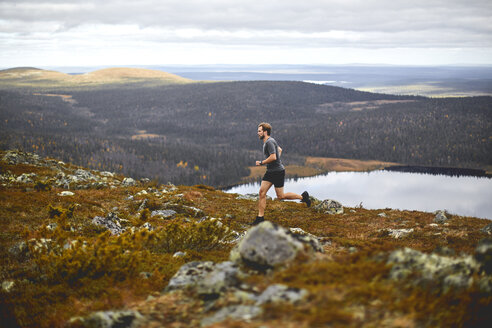 Man trail running on rocky cliff top, Keimiotunturi, Lapland, Finland - CUF20115