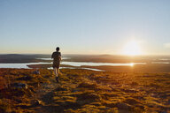 Man trail running on cliff top at sunset, Keimiotunturi, Lapland, Finland - CUF20118