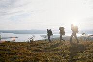 Hikers crossing field by lake, Keimiotunturi, Lapland, Finland - CUF20130
