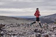 Man trail running on rocky cliff top, Kesankitunturi, Lapland, Finland - CUF20136