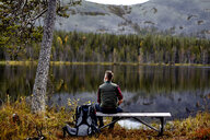Hiker resting on bench, looking out at lake, Kesankijarvi, Lapland, Finland - CUF20142
