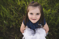 Girl sitting on grass looking up at camera smiling - CUF20145
